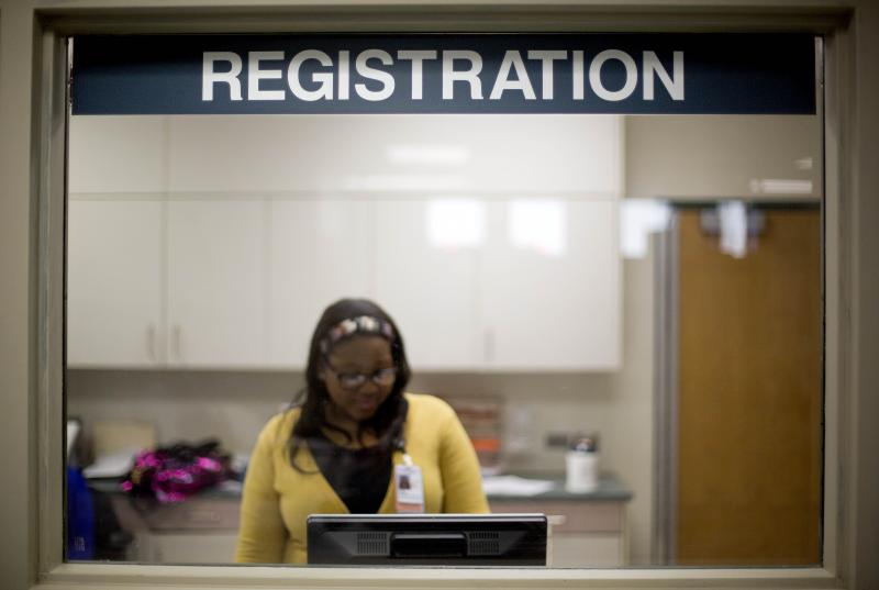 A worker is seen behind the registration window of the emergency room at Grady Memorial Hospital in Atlanta.