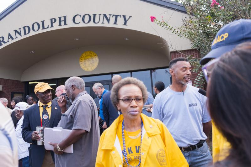 Opponents to the plan to shutdown seven of nine polling places in Randolph County wait to get into the government center for the vote on the plan Friday morning.