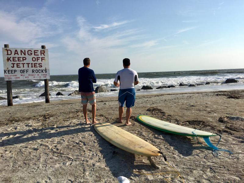 Surfers contemplating waves at Tybee Island.
