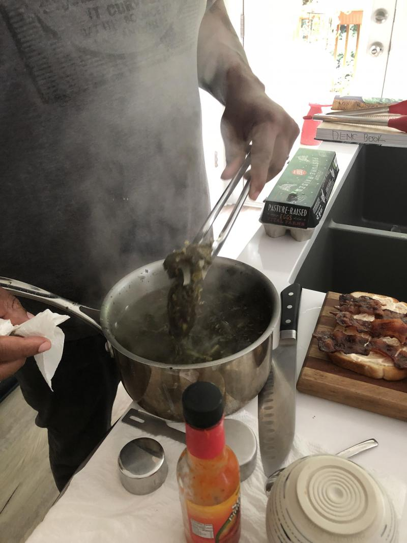 Todd Richards cooks collard greens in his home kitchen in Atlanta.