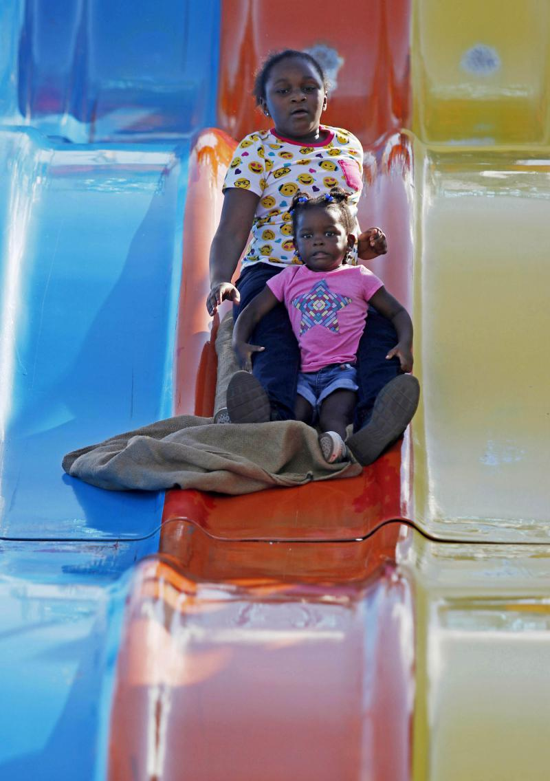 Londyn Blithers, 3, and Nicole Greene, 9, from Atlanta, Georgia, slide down a ride during the Georgia National Fair in Perry, Georgia, on Saturday, Oct. 6, 2018. The Georgia National Fair is celebrating its 29th anniversary this year.