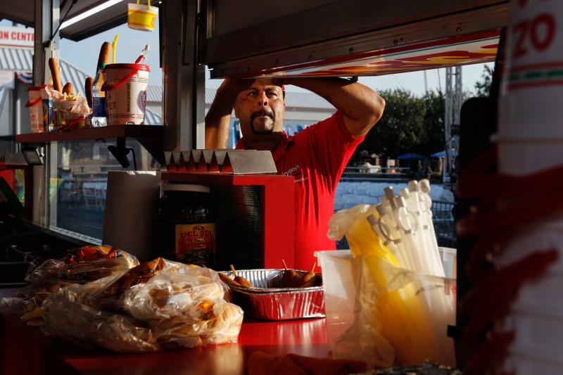 Chris Shelton, a 42-year-old concession worker from Knoxville, Tennessee, prepares for a work day by opening up a concession stand at the Georgia National Fair in Perry, Georgia, on Saturday, Oct. 6,  2018.