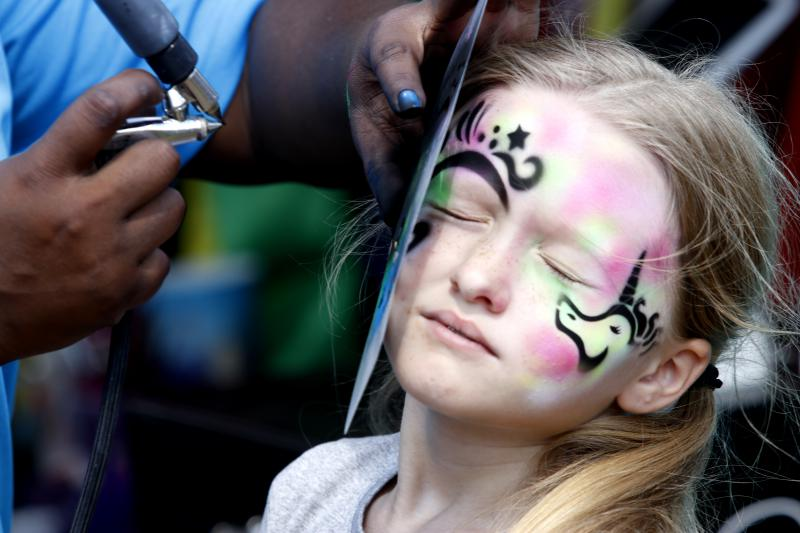 Presely Neesmith, 8, gets her face painted by Amber Wright, 25, at the Georgia National Fair in Perry on Saturday. This was Wright's first week working at the fair and she enjoyed doing the airbrush face painting because she wants to be an artist.
