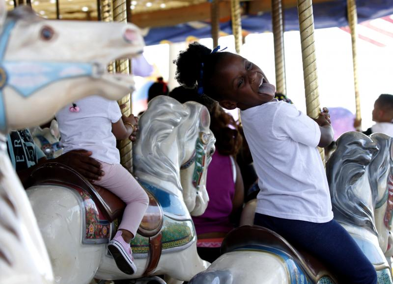 Jamiah Howe makes a face to her family as she rides the merry-go-round at the Georgia National Fair in Perry on Saturday. Howe and her family are from Locust Grove and this is their first time at the Georgia National Fair.