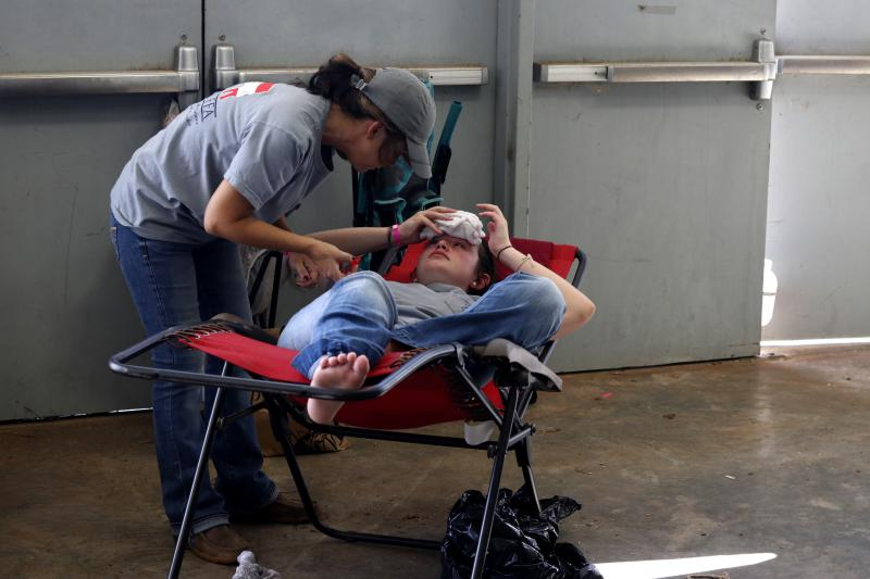 """Maddie Grace Martin, 14, of Jefferson, rests in the shade at the Georgia National Fair on Saturday. """"She got a little overheated,"""" said her mother, Misty Martin."""