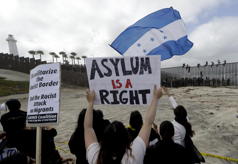 Central American migrants sit on top of the border wall on the beach in San Diego during a gathering of migrants living on both sides of the border.