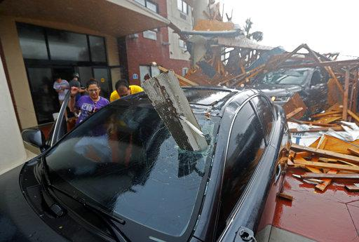 A woman checks on her vehicle as Hurricane Michael passes through, after the hotel canopy had just collapsed, in Panama City Beach, Fla., Wednesday.