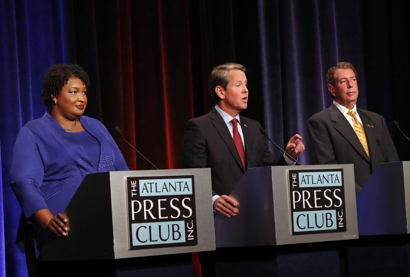 Republican gubernatorial candidate for Georgia Secretary of State Brian Kemp, center, speaks as Democrat Stacey Abrams, left, and Libertarian Ted Metz look on during a debate Tuesday, Oct. 23, 2018, in Atlanta.