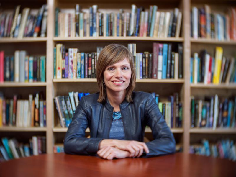Lisa Yaszek, professor of science fiction studies, in front of a bookshelf seated at a table.