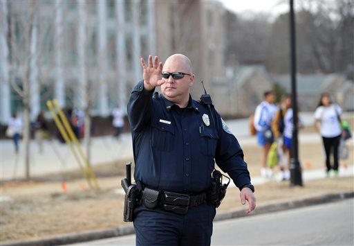 A police officer stops traffic in front of Chamblee Charter High School after a youth was arrested for carrying loaded guns, according to authorities, on Tuesday, Feb. 18, 2014, in Chamblee, Ga.