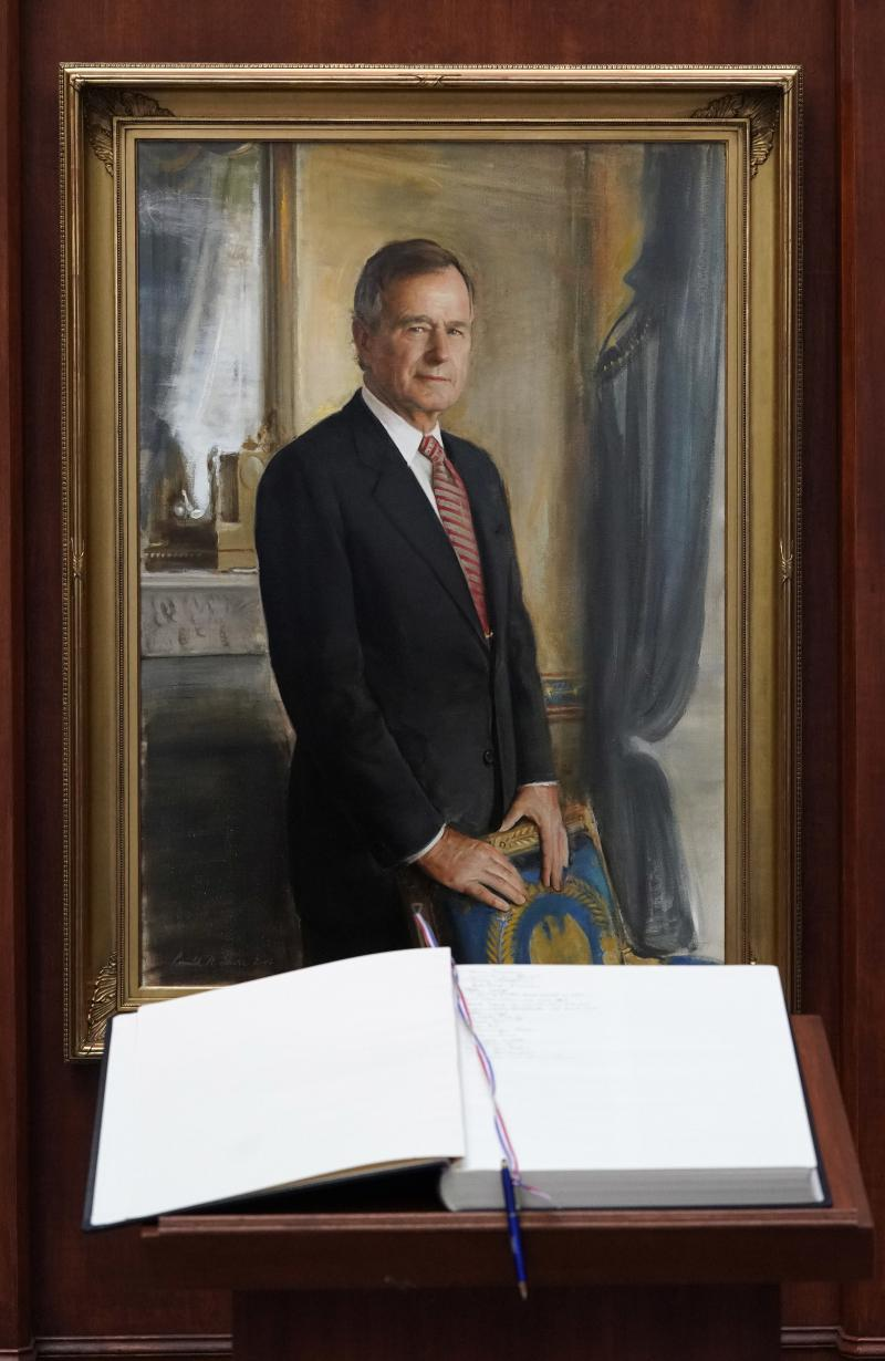 A condolence book sits in front of a painting of George H.W. Bush inside the George H.W. Bush Library and Museum Saturday, Dec. 1, 2018, in College Station. Bush has died at age 94.