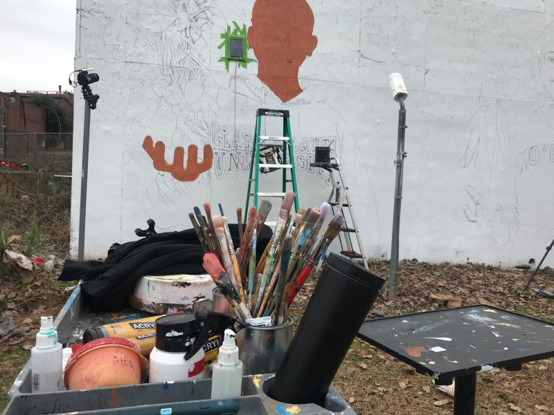 Yungai's paintbrushes sit in front of the wall where he paints his mural.