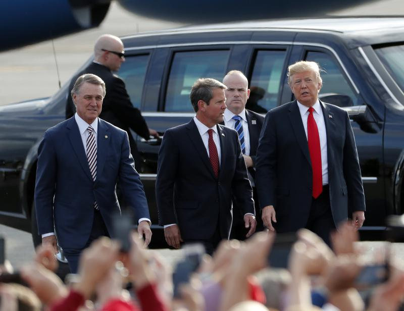 Brian Kemp, center, walks with President Donald Trump, right, and Sen. David Perdue (R-Ga) as Trump arrives for a rally in Macon.