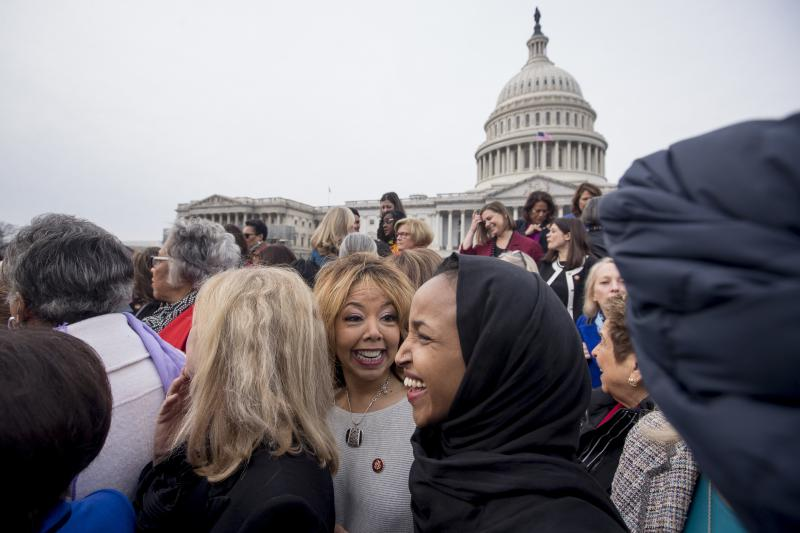 Rep. Lucy McBath, D-Ga., center, smiles with Rep. Ilhan Omar, D-Minn., second from right, following a group portrait in Washington as the 116th Congress begins.