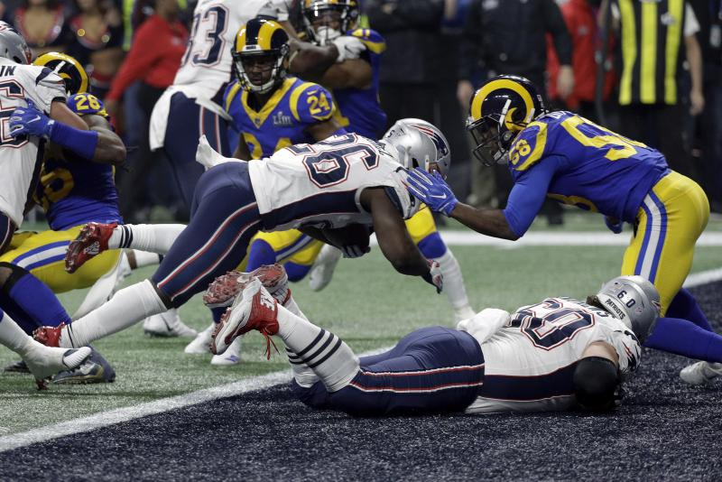 New England Patriots' Sony Michel (26) dives over the goal line for a touchdown in front of Los Angeles Rams' Cory Littleton (58) during the second half of the NFL Super Bowl 53 football game Sunday, Feb. 3, 2019, in Atlanta.