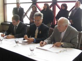 Lansing Mayor Virg Bernero (far left), Sault Ste. Marie Tribe of Chippewa Indians Chairperson Aaron Payment and private investor Bob Liggett sign a land sale agreement that turns over city-owned property adjacent to the Lansing Center to the tribe.
