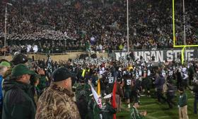 The MSU football team celebrates with the Spartan Marching Band and the student section after beating Michigan on Saturday.