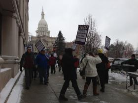 Dozens of public employee union members protest Tuesday outside Governor Rick Snyder's office, across from the state Capitol in Lansing.