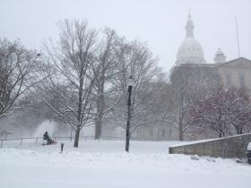 Over a foot of snow blankets the lawn of the Michigan capitol building.
