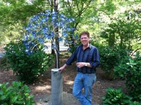 "Craig Mitchell Smith at Norfolk Botanical Gardens in Virginia during his 2012 show. Craig is in the process of installing ""The Hydrangea"" floral sculpture."
