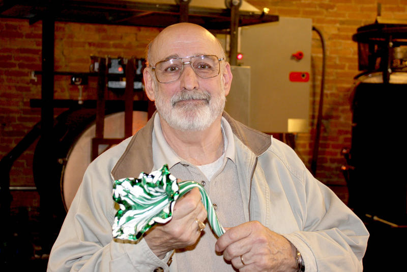 John Snyder poses with a floral piece similar to the one he just crafted at Fireworks Glass Studio.