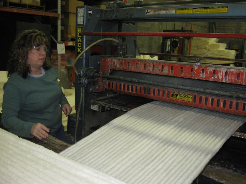 Rachelle Padgett feeds a sheet of corn starch through a roller during the production phase.  KTM Industries is the only company in the world that makes this particular product.