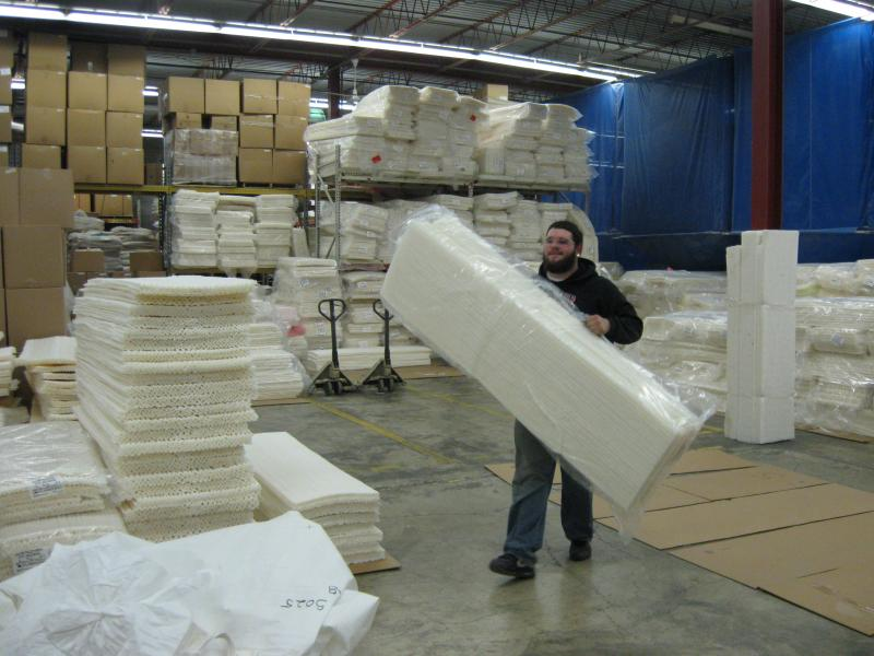 KTM's Jake Laraway carries a bundle of insulating foam to an awaiting cargo truck.