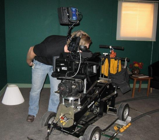 A production crewman checks a camera on a student-built film set at Michigan State University.