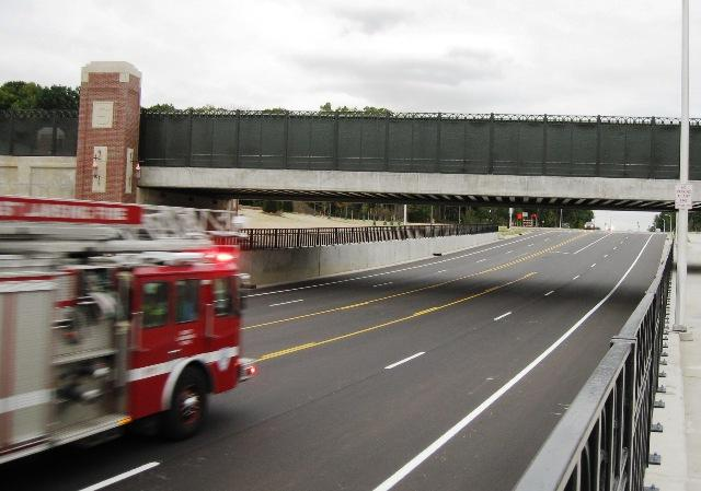 A fire truck rushes beneath the Farm Lane railroad bridge on the first day the road re-opened for traffic.