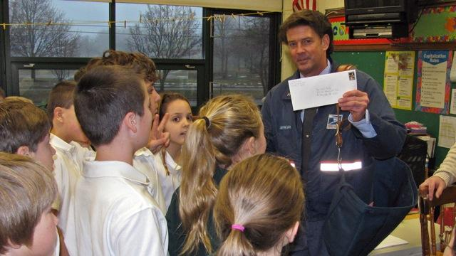 Postman Dave Randall with students at St. Thomas Aquinas Parish School.