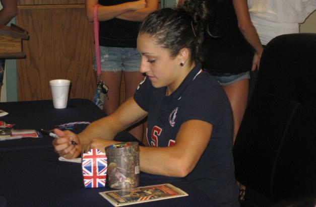 Gymnast Jordyn Wieber signs an autograph for a fan at a fundraiser to help her family attend the Olympic Games in London.