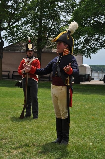 Re-enactors depict an American officer and a member of the British infantry of 1812.