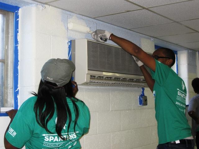 MSU senior Ronald Taylor (right) stretches to reach a tough spot while painting at Advent House Ministries in Lansing.