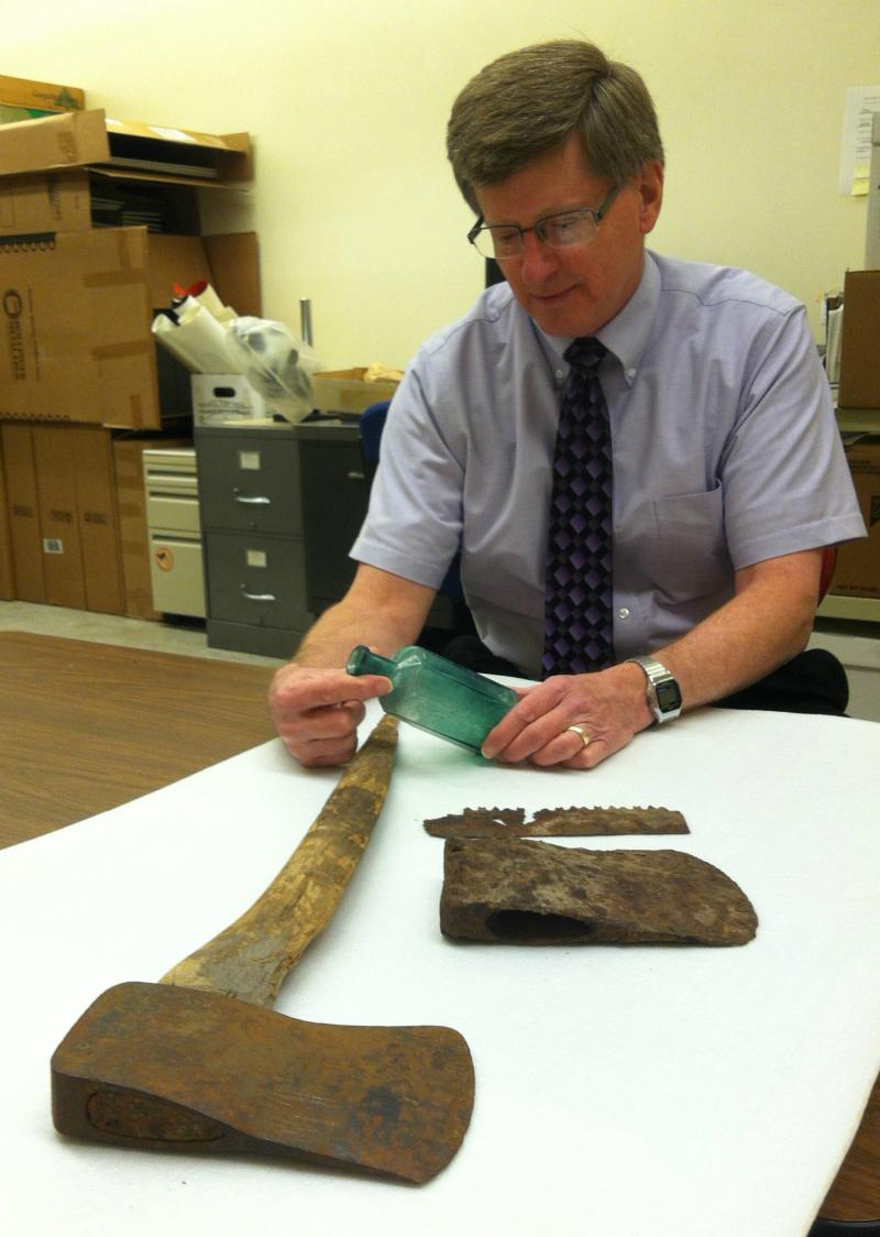 State Archaeologist Dr. Dean Anderson examines artifacts from an abandoned iron smelting site in now deserted Fayette, Michigan.