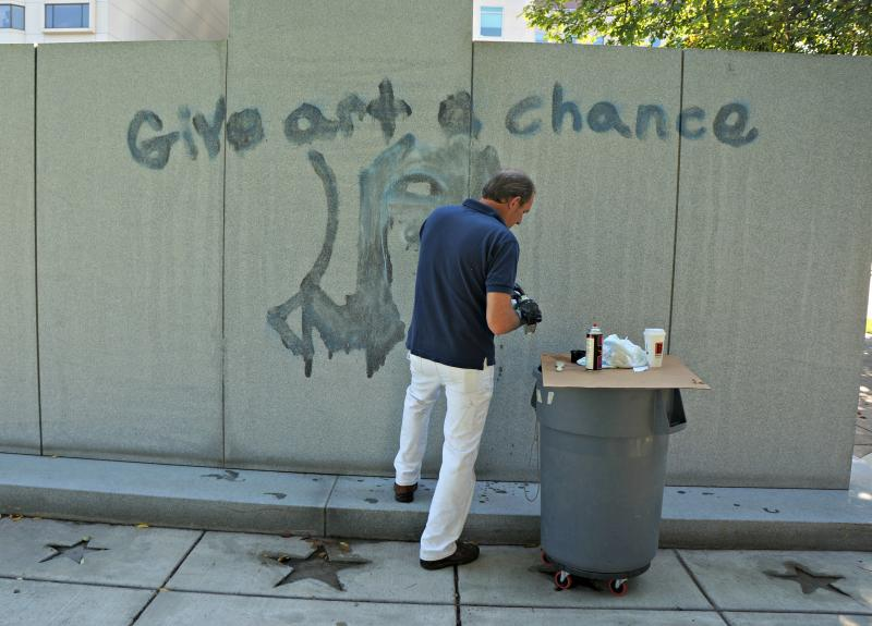 Capitol employee Greg Hess tries to scrub graffiti off war memorial on Thursday.