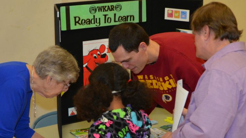 WKAR's Beany Tomber meets a family at the Ready To Learn booth.