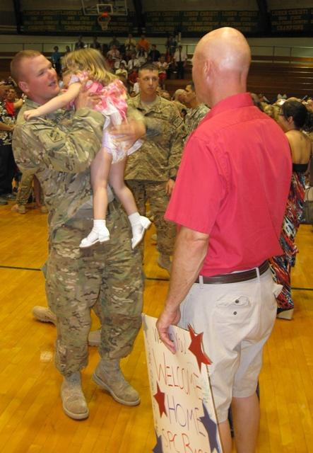 Spc. James Bassett embraces his daughter after a nine-month tour in Afghanistan.