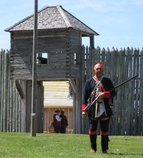 A re-enactor dressed as an Ojibwe warrior guards the land gate at Fort Michilimackinac.