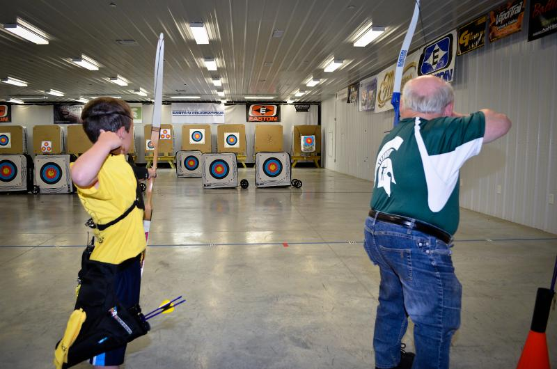 Liam Smith and Len Sawisch practice archery at the MSU Demmer Center.