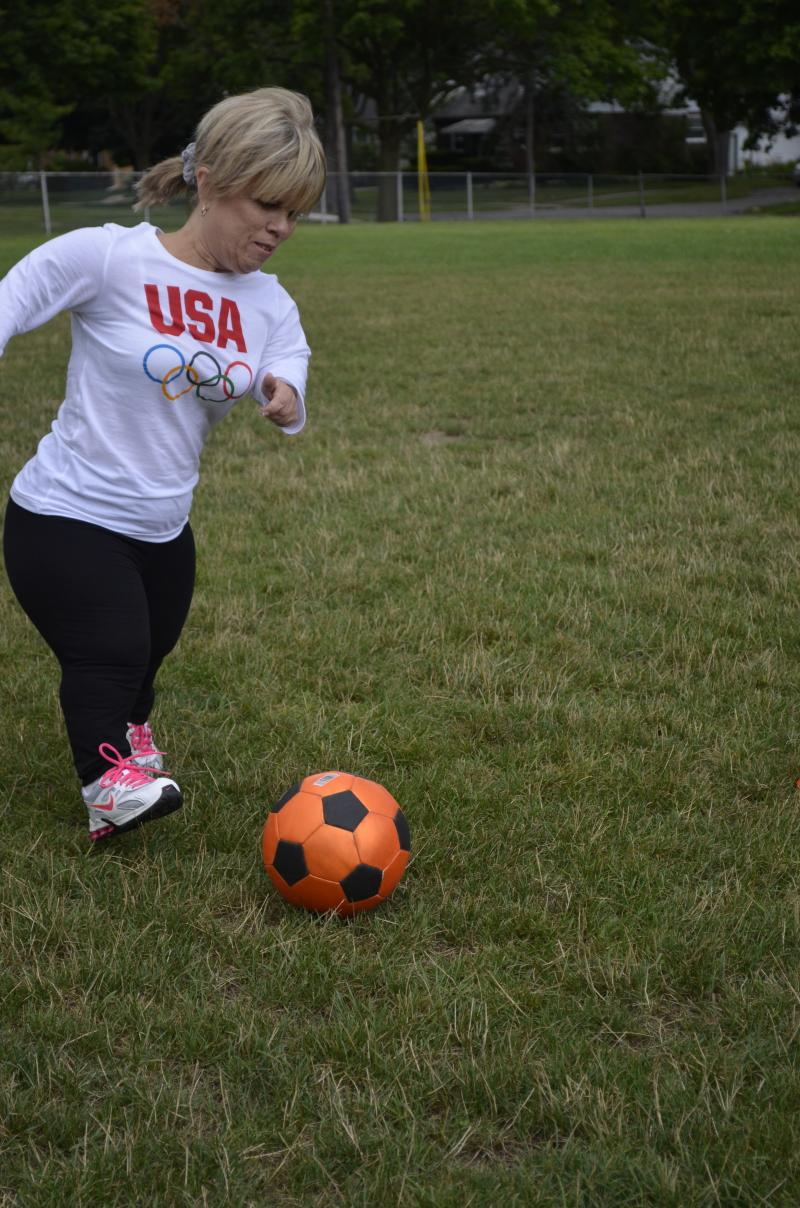 Amy Andrews, President of the Dwarf Athletic Association of America and World Dwarf games competitor, kicks the ball up the field during soccer practice.