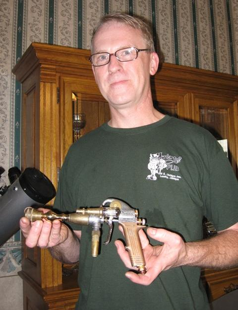 "Tim Higgins brandishes a ""steampunk"" ray gun fashioned from brass tubing."