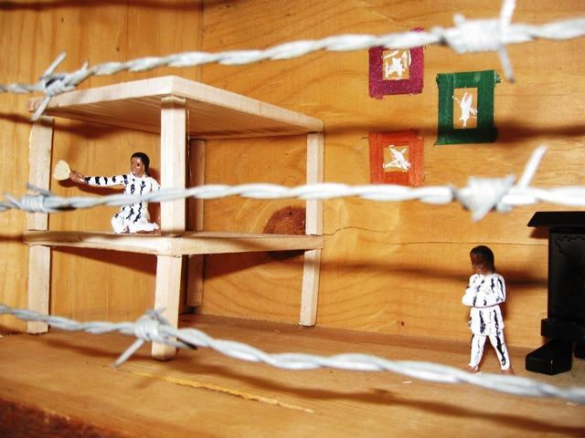 Inside a wooden box, this model represents concentration camp housing, complete with barbed wire.