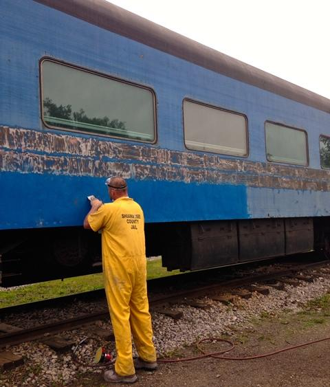 A Shiawassee County Jail work release program provides help with tasks like sanding paint off a rail car.
