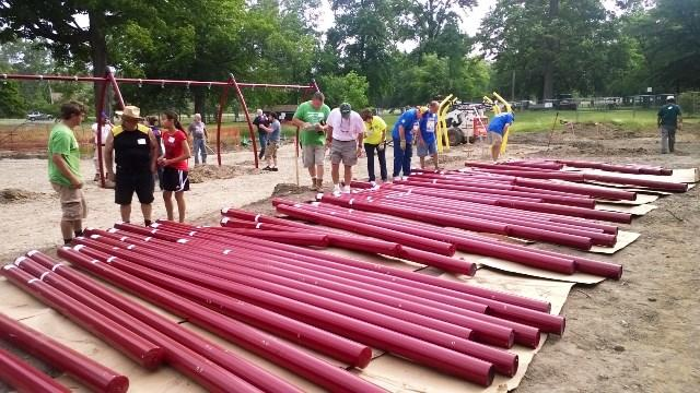 Volunteers work on the new playground equipment at Patriarche Park.