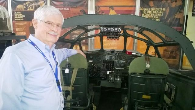 Retired U.S. Navy pilot Randy Hotton stands beside a replica of the cockpit of a B-24 Liberator.  During the war, Willow Run turned out one B-24 every hour.
