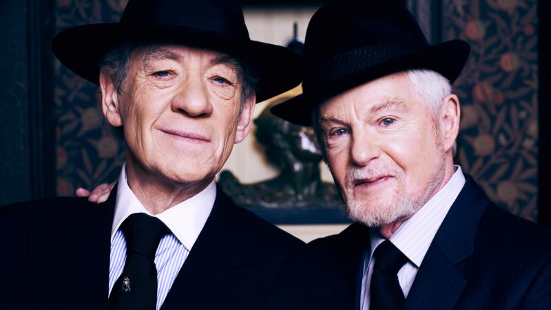 Two men in suits with hats