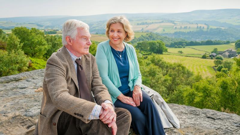 Couple sitting on scenic hillside