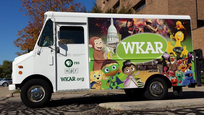 Truck with WKAR logo and collage of people, places and characters