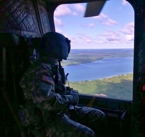 A soldier gazes at Lake Margrethe on an airborne mission over Camp Grayling in northern Michigan.