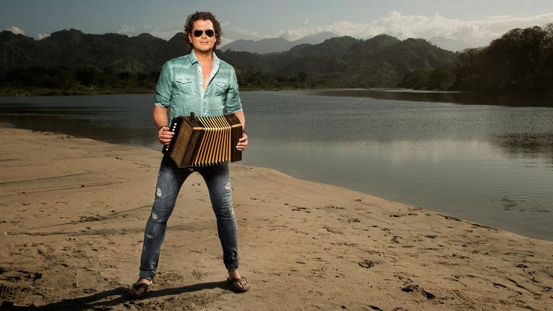 Man with accordian with lake and mountains in background